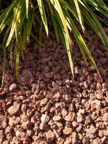 Grava volcánica rojiza instalada en jardín